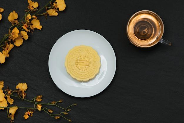 Słodki kolor śnieżnej skóry mooncake i filiżanka herbaty z kwiatami.