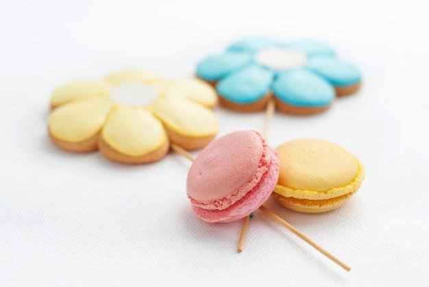 Słodki kolorowy makaronik z ciasteczkami w kształcie kwiatka na białym stole. desery na dobry nastrój do herbaty. mała głębia ostrości