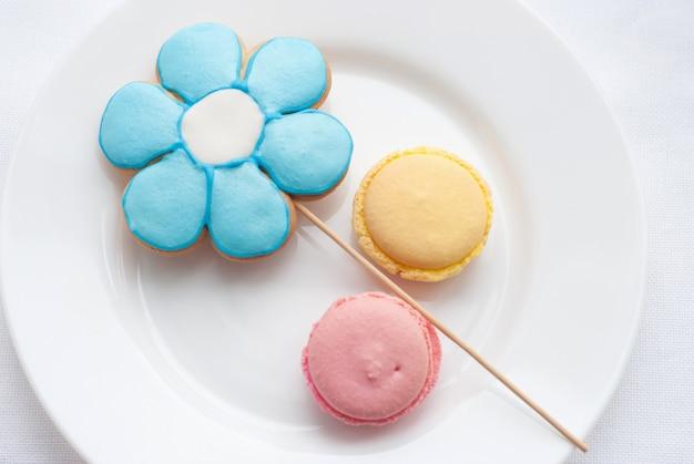 Słodki kolorowy makaronik z ciasteczkami w kształcie kwiatka na białym talerzu. widok z góry. desery na dobry nastrój do herbaty