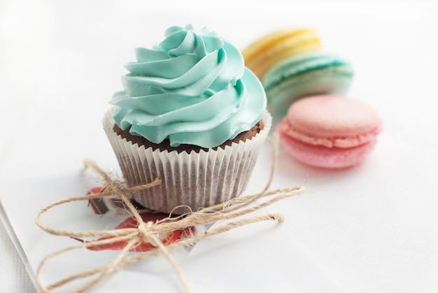 Słodki kolorowy makaronik z ciastko na białym stole. desery jako prezent na dobry nastrój