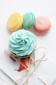 Słodki kolorowy makaronik z ciastko na białym stole. widok z góry. desery jako prezent na dobry nastrój