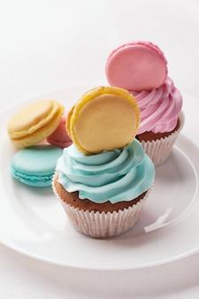 Słodki kolorowy makaronik z posypką na białym talerzu. desery jako prezent na dobry nastrój