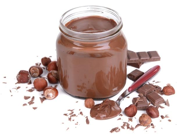 Słodki krem czekoladowy w słoiku na białym tle