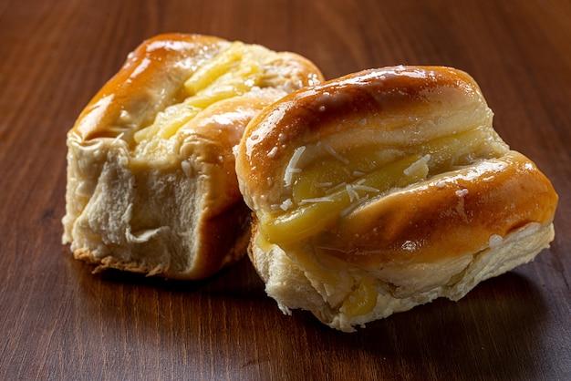 Słodki krem waniliowy chleb na brązowym drewnianym stole. jest to rodzaj chleba powszechnego w brazylii i portugalii, wyrabiany ze słodkiego ciasta.
