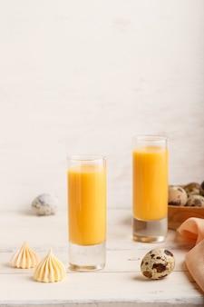 Słodki likier jajeczny w szkle z jajkami przepiórczymi i bezami na białej drewnianej powierzchni. widok z boku, kopia przestrzeń, w pionie.