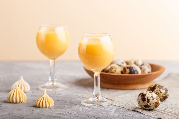 Słodki likier jajeczny w szkle z jajkami przepiórczymi i bezami