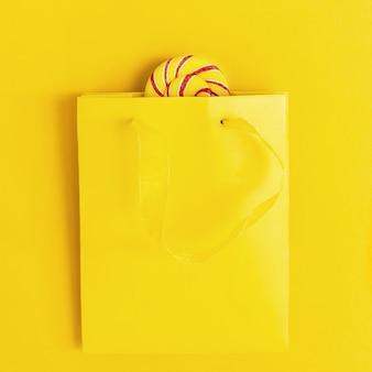 Słodki lizak z cukierkami w jasnych kolorach wystaje z żółtej papierowej torby