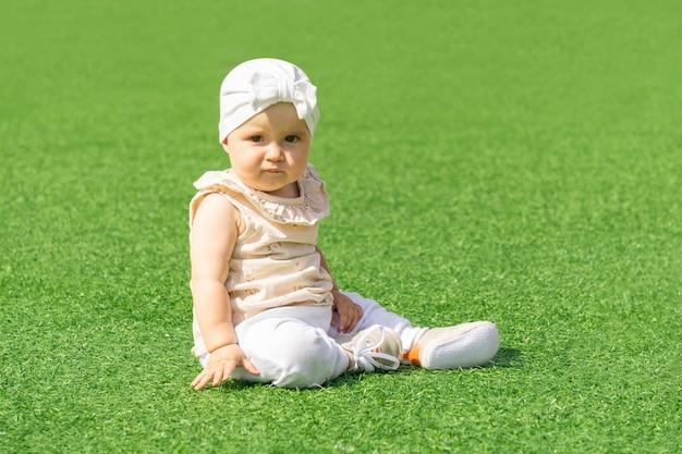 Słodki maluch siedzący na zielonym trawniku