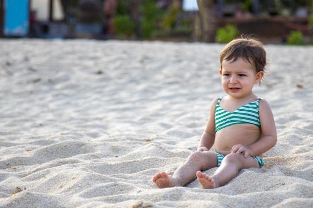 Słodki maluch w kostiumie kąpielowym siedzi na piaszczystej plaży w słońcu