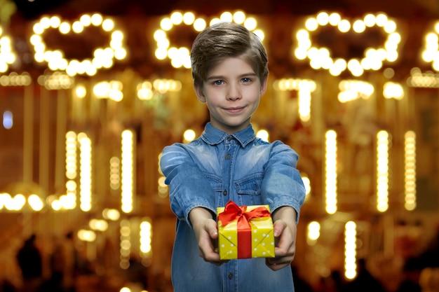 Słodki mały chłopiec daje ci prezent