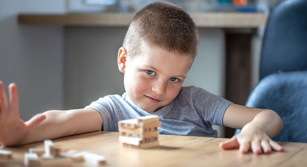 Słodki mały chłopiec gra w grę planszową z drewnianymi kostkami i wieżyczką.