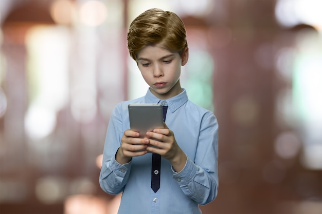 Słodki mały chłopiec patrzy na smartfona