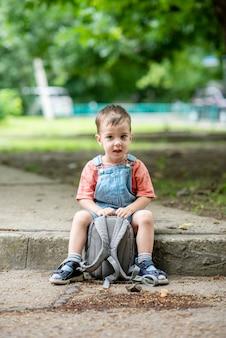 Słodki mały chłopiec patrzy w kamerę trzyma w rękach torbę ubrany w dżinsowe kombinezony earl ear