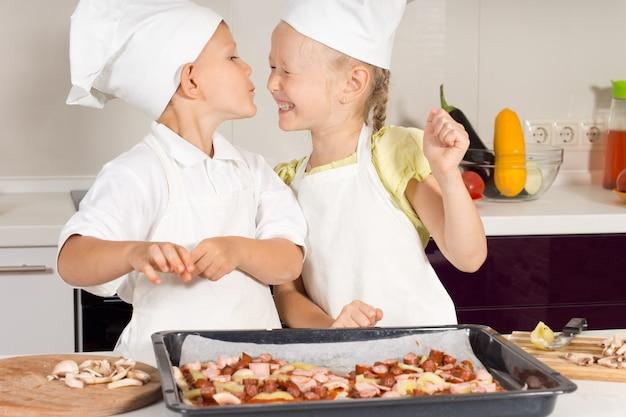 Słodki mały kucharz całuje swoją siostrę kucharza w kuchni. bardzo szczęśliwe dzieci.