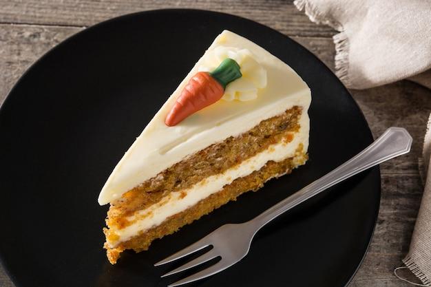 Słodki marchwianego torta plasterek na talerzu na drewnianym stole