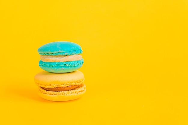 Słodki migdałowy kolorowy jednorożec niebieski żółty makaronik lub makaronik tort na białym tle na modny żółty nowoczesny sposób