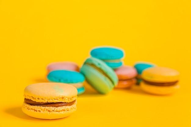 Słodki migdałowy kolorowy jednorożec różowy niebieski żółty zielony makaronik lub makaronik tort na białym tle na modny żółty nowoczesny sposób