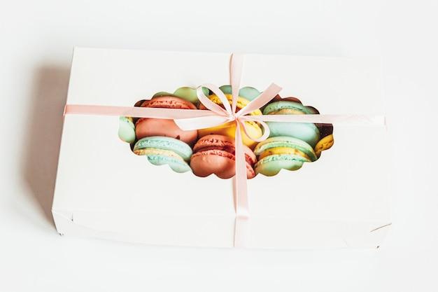 Słodki migdałowy kolorowy różowy niebieski żółty zielony macaron lub makaronik deser ciasto w pudełku na białym tle na biały stół. francuskie słodkie ciasteczko. minimalna koncepcja piekarni żywności. widok z góry płasko leżał, miejsce na kopię