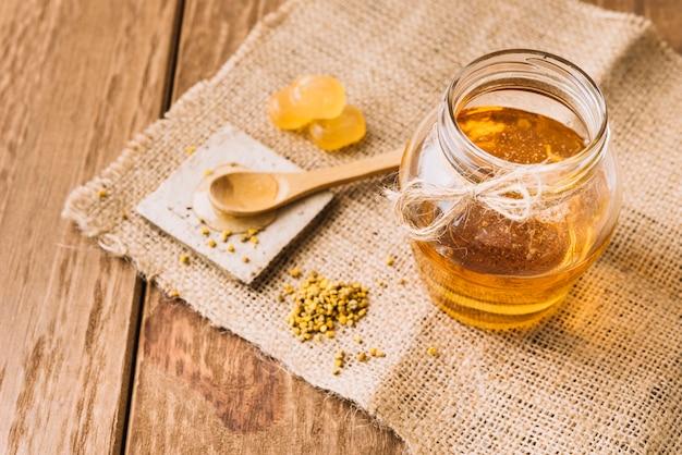 Słodki miód; pszczoła nasiona pyłku i cukierki na płótnie worek