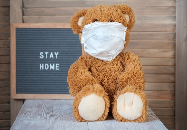 Słodki miś w masce medycznej na szarej filcowej tablicy z tekstem zostaje w domu. koncepcja kwarantanny domowej podczas pandemii koronawirusa covid-19