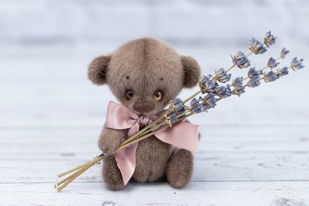 Słodki miś z różową kokardką siedzi na wiklinowym tle i trzyma bukiet suszonych kwiatów lawendy.