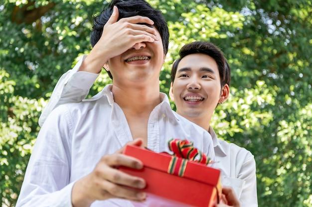 Słodki moment miłości. portret azjatyckiego homoseksualnego uścisku i niespodzianki prezent dla chłopaka. koncepcja gejów lgbt.