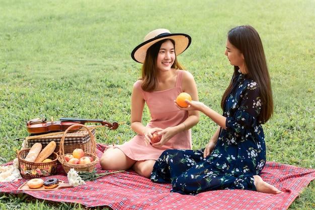 Słodki moment miłości. portret azjatyckiej pary homoseksualnej, grającej ze skrzypcami i piknikiem w parku. koncepcja lgbt leasbian.