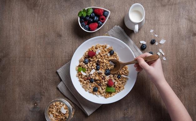 Słodki musli z jagodami w talerzu z mlekiem na drewnianym stole.