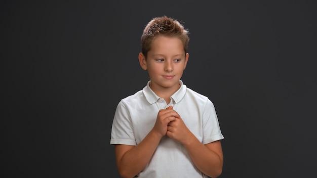 Słodki niewinny chłopiec w białej koszuli trzymający ręce razem przed sobą, patrząc z ukosa w dolny róg