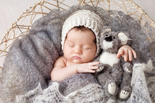 Słodki noworodek śpi w koszu. piękny noworodek chłopiec z zabawką miś.