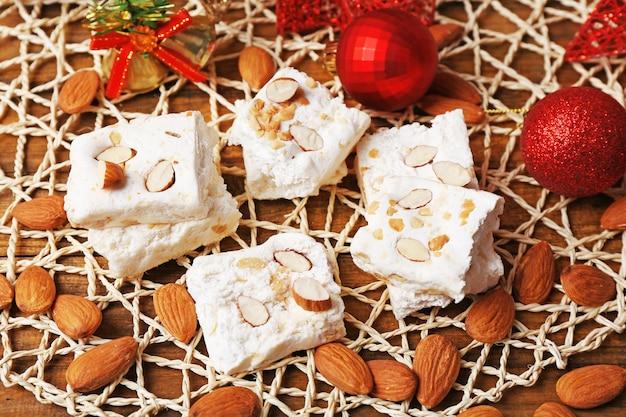 Słodki nugat z migdałami i świąteczną dekoracją stołu z bliska