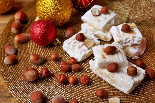Słodki nugat z orzechami laskowymi i świąteczną dekoracją stołu z bliska