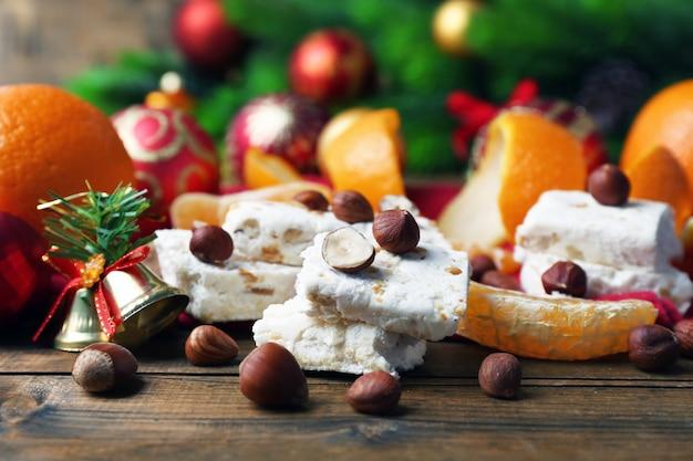 Słodki nugat z pomarańczami i świąteczną dekoracją na stole z bliska