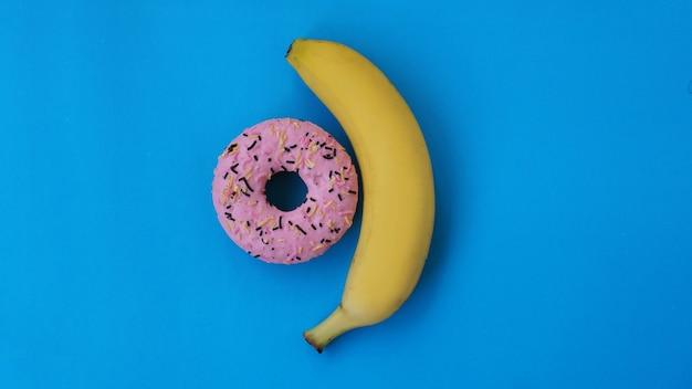 Słodki pączek i banan na niebieskim tle