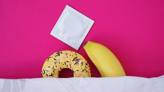 Słodki pączek i banan na różowy kolor tła. koncepcja erotyczna. banan przytula pączka w łóżku