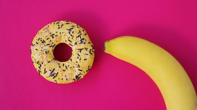 Słodki pączek i banan na różowy kolor tła. seks i koncepcja erotyczna