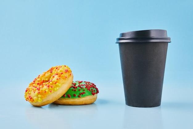 Słodki pączek lub pączek z filiżanką gorącej świeżo parzonej kawy lub herbaty. kubek papierowy na wynos z pączkami.