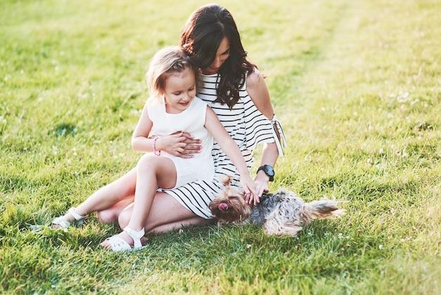 Słodki pies bawi się z matką i córką na zewnątrz w polu
