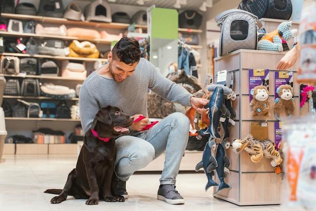 Słodki pies z właścicielem w sklepie zoologicznym