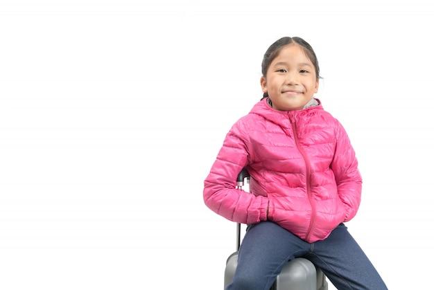Słodki podróżnik nosi różową kurtkę puchową i siedzi na walizce