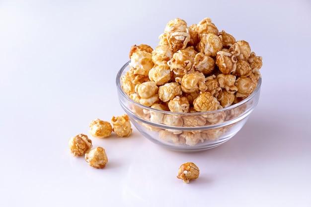 Słodki popcorn karmelowy w szklanej misce. ścieśniać. biała przestrzeń. izolować.