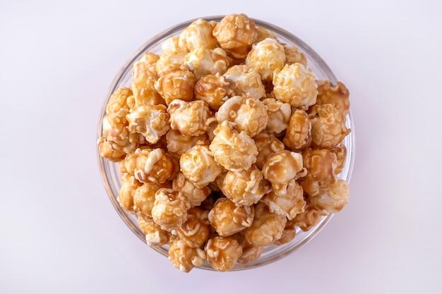 Słodki popcorn karmelowy w szklanej misce. ścieśniać. biała przestrzeń. widok z góry.