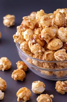 Słodki popcorn karmelowy w szklanej misce. ścieśniać. ciemnoszara przestrzeń.