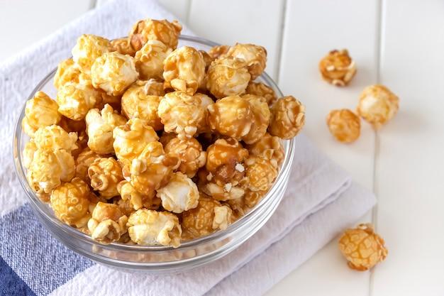 Słodki popcorn karmelowy w szklanej misce. ścieśniać. jasna przestrzeń.