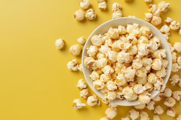 Słodki popcorn na żółtym tle