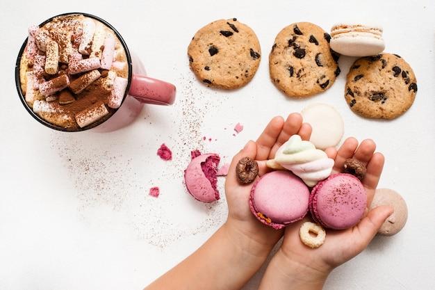 Słodki poranek z gorącym kakao i ulubionymi ciasteczkami. nierozpoznane dziecko z kolorowymi makaronikami w dłoniach, czekoladową bułeczką i pysznym napojem z pianką na białym stole w pobliżu, widok z góry