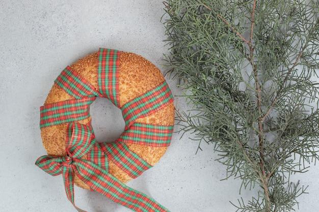 Słodki pyszny bajgiel zawiązany w świąteczną kokardkę na wiązce choinki