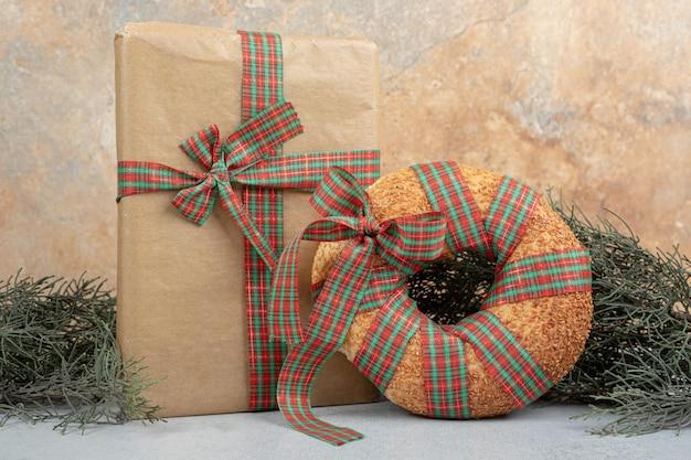 Słodki pyszny bajgiel zawiązany w świąteczną kokardkę z prezentem bożonarodzeniowym.