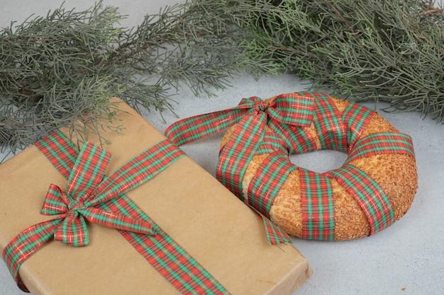 Słodki pyszny bajgiel zawiązany w świąteczną kokardkę ze świątecznym prezentem