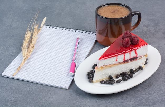 Słodki pyszny kawałek ciasta z kartką papieru na szarym stole.
